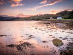 The light of a setting sun paints both the sky and water around Rockpool House with pink shades