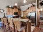Highback leather breakfast chairs, stainless steel appliances and full kitchen.