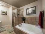 Master bathroom with roman jetted tub and glass shower.