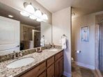 Guest bathroom with full wall mirror, dual sinks and jetted tub and glass encased shower.