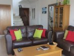 Lounge area with two double settees and television.