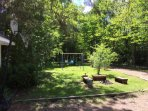 Spacious lawn with swing set, basket ball net and fire pit