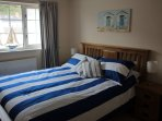 Master bedroom with king bed, travel cot and window overlooking harbour