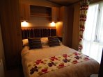 master bedroom with wardrobes, drawers, overbed cuoboards, dressing table & en-suite toilet