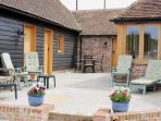 Patio area with comfy chairs and dining table and chairs. BBQ and washing line.