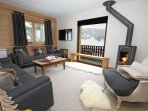 Large open plan first floor reception room with stunning piste views and log fire, flat screen TV