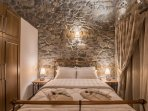 Stonebuilt bedroom with a double bed. Deluxe villa