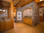 Kitchen with double ovens and glass cooktop.