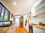 Large modern kitchen equipped with dishwasher, stove top, oven, coffee machine, fridge and microwave