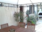 Curtained pergola just outside the rear door, with table and chairs, showing the BBQ