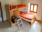 Habitación 3. Cama tipo litera y cama individual. Armario y cómoda.
