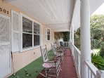 The right half of the roofed in front porch w/plenty of rocking chairs