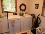main floor laundry room with bin for hot tub items