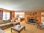 The inviting living room features comfy furniture in front of a cozy fireplace.