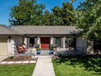 Inviting front porch with seating area faces large community park with playground, basketball & more