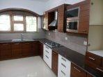 Modern kitchen with hob, hood, sink, microwave, fridge, washing machine.