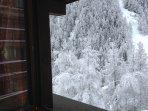 Snowy mountain view through the balcony door
