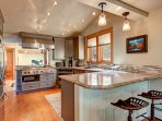 Fully-equipped modern kitchen with granite counters, stainless appliances, and bar seating