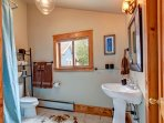Guest bathroom with pedestal sink and clawfoot tub with shower