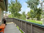 Roomy deck with gas grill and bench seating opens to beautiful green space.