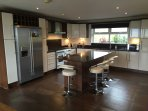 Luxury fully fitted Kitchen. Open plan to dining area with double sided wood burning stove
