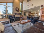 """The main floor living room features leather furnishings, 40"""" HDTV, entertainment center, gas fireplace and mountain..."""