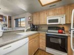 The renovated kitchen features a complete range of household appliances including a fridge, stove, dishwasher...