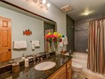 The guest bathroom on the main level is quite spacious, with a single vanity and shower/tub combo.