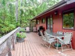 Large wrap around deck with a BBQ, surrounded by woods and wild rhododendrons.
