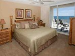 King master bedroom with beach-style furniture suite and sliding glass doors to Gulf-front patio