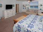 Spacious master bedroom with King bed, plush carpeting and colorful decor and accents