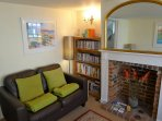 Comfy, well furnished room. 2 seater sofa, 3 seater sofabed, armchair, footstool. Leads to hallway.