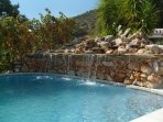 Large swimming pool 13 mtr x 6 mtr one depth all over with a natural stone built waterfall.