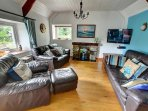 The living room has large leather brown sofas, open fire and Freeview TV