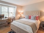 Third floor bedroom with a queen size bed, closet, desk and plenty of light