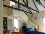 living room has exposed beam cathedral ceiling