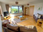 Leather suites and solid oak furniture with views over the garden and loch.