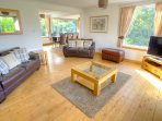 Very spacious open plan downstairs living/ dining room with lovely views over the garden and loch.