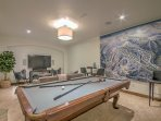 Another view of lower living with pool table with ping pong top, bar tables, wet bar