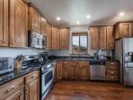 The gourmet kitchen features a complete range of stainless steel appliances including gas stove, dishwasher...