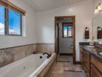 The en suite bathroom is equipped with a his and hers vanity with granite counters, hardwood cabinetry, large walk-in...