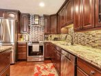 Kitchen includes stainless steel appliances, granite countertops and wine cooler.