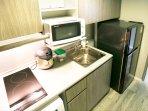 Hotplates, hood, kettle, microwave, sink, and fridge