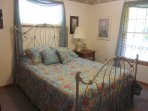 The main-level queen room features a romantic iron bed with memory foam mattress & lovely antiques.