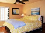 Bedroom 1 is bright and cheery, flat screen TV mounted on wall, has walk out to balcony/patio