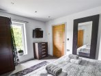 The master bedroom has contemporary furnishings and a wall-mounted TV