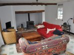 Comfortable airy sitting room with French doors to garden, wood burning stove, books, tv/dvd player