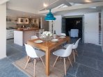 Vaulted dining room with beams, slate floor with underfloor heating. Wooden table with Eames Chairs