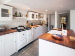 Galley kitchen with Aga, conventional hob & oven.  Sink in the island -