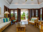 The living room features French doors that open onto the pool deck